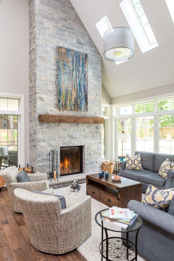 un salon neutre propre à double hauteur avec une cheminée en pierre grise avec un manteau en bois et une œuvre d'art bleu vif
