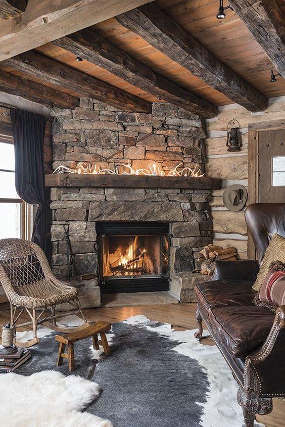un salon avec une cheminée en pierre, des bois sur le manteau, des tapis superposés et des meubles en osier et en cuir