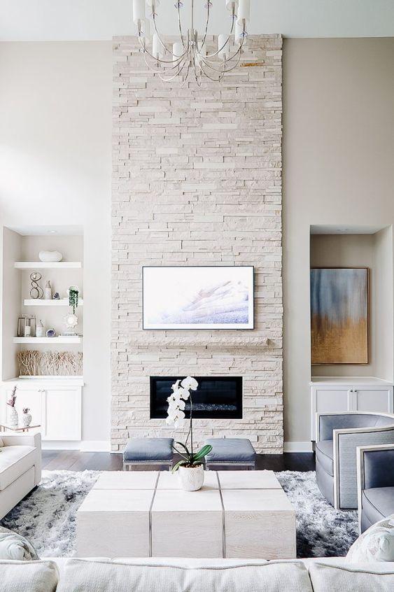 un salon propre et neutre avec une cheminée en faux pierre blanche et quelques touches bleu pastel ici et là