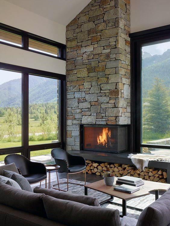 un salon cabine contemporain avec une cheminée en pierre et un rangement pour le bois de chauffage, des meubles chics et beaucoup de fenêtres