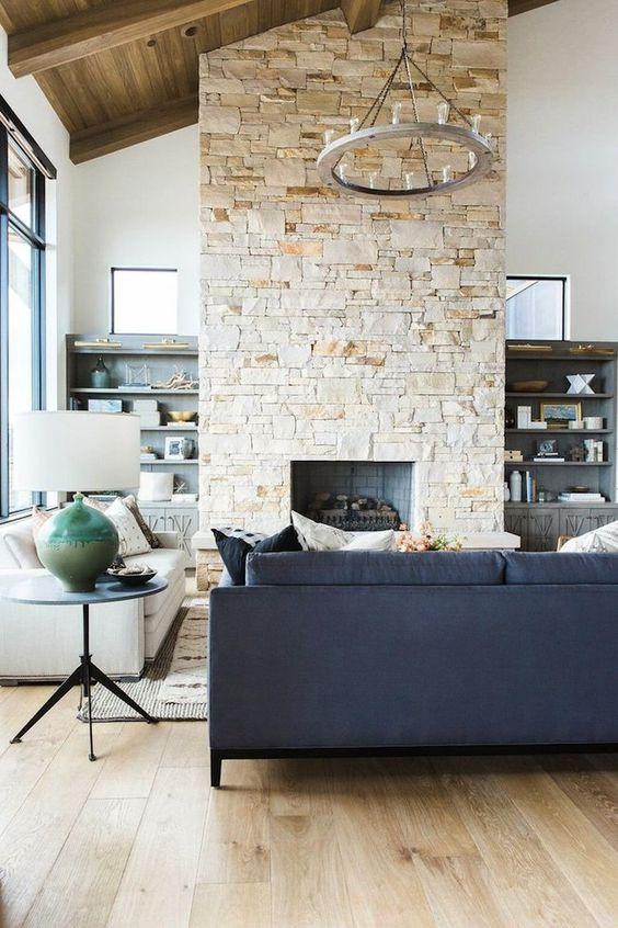 un salon contemporain aux tons neutres, avec un plafond double hauteur, une cheminée en pierre qui réchauffe l'espace
