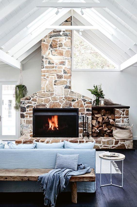 un salon contemporain avec des meubles bleus, un foyer en pierre avec une cheminée moderne intégrée et des puits de lumière