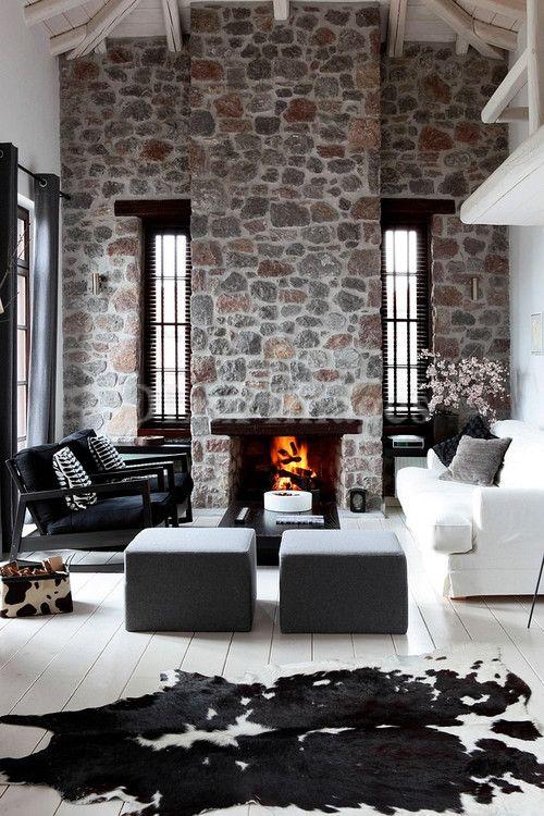 un espace contemporain monochromatique avec des murs en pierre lumineuse et une cheminée, un mobilier noir et blanc élégant et laconique