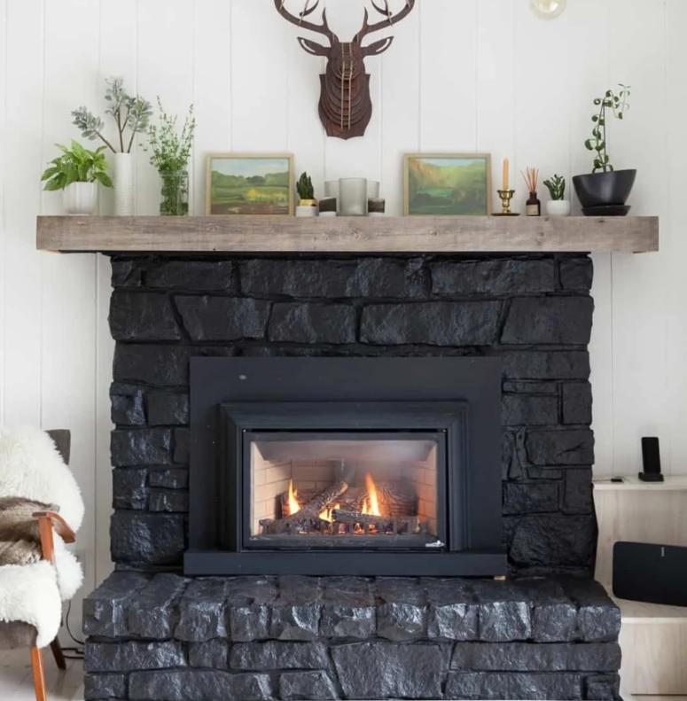 une grande cheminée revêtue de pierre noire avec un manteau en bois est une excellente touche de cabane ou de bois à l'espace