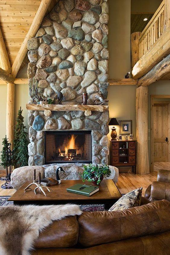 un magnifique espace cabine avec une grande cheminée en pierre avec des pierres à sa base, des meubles en cuir et en bois