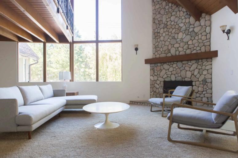 un espace minimaliste neutre et propre avec une cheminée en pierre d'angle originale avec un manteau en bois teinté foncé