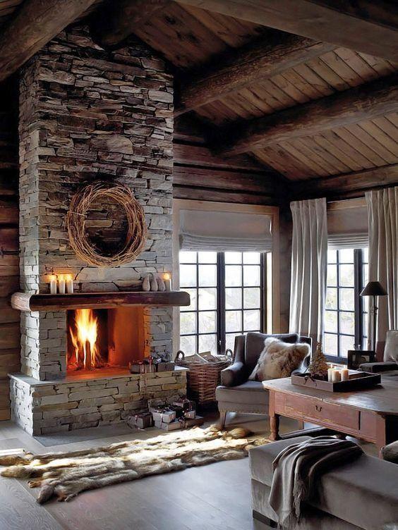 un salon neutre de mauvaise humeur avec une cheminée en pierre grise, des meubles vintage, des tapis en fausse fourrure et des couvertures et des bougies