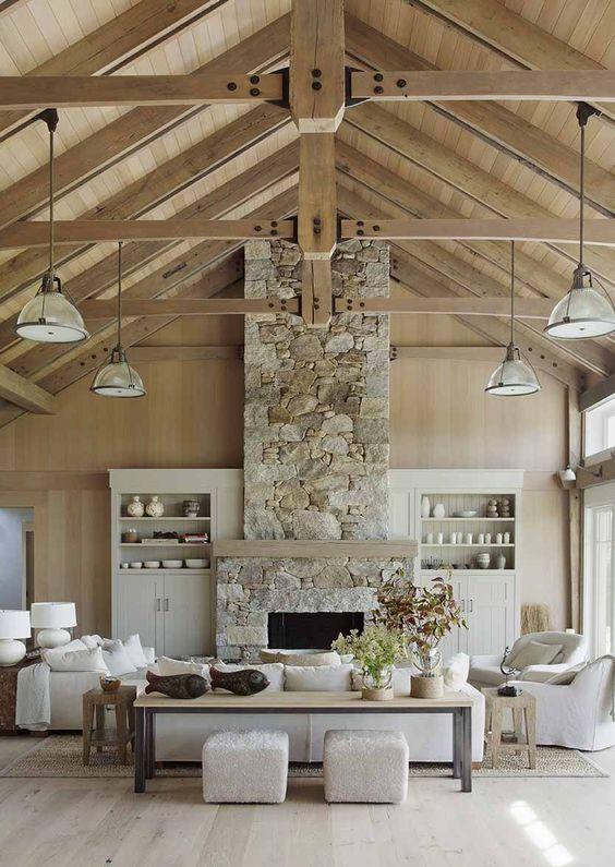 un salon contemporain neutre agrémenté d'une cheminée en pierre neutre et de poutres en bois