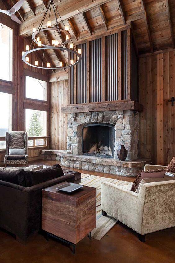 un salon cabine élégant et chic avec de riches bois teintés, une cheminée en pierre et en métal et des meubles vintage