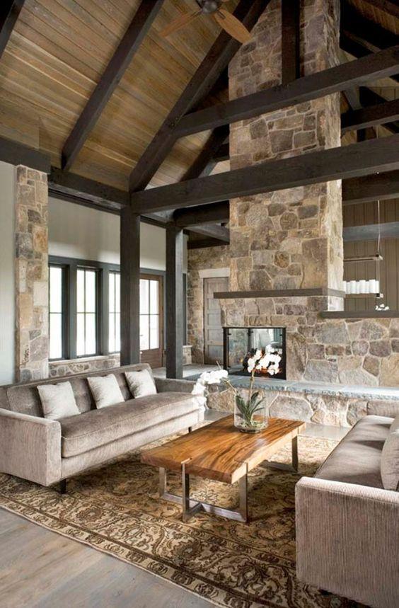 un salon cabine contemporain neutre avec cheminée en pierre double face, mobilier neutre, poutres en bois