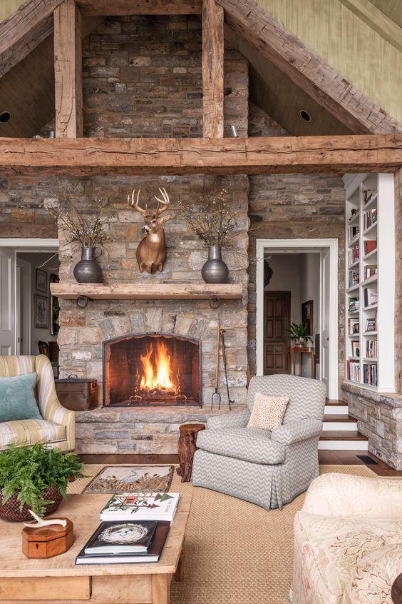 un salon cabine accueillant avec des murs en pierre et une cheminée, des poutres en bois, un tapis de jute et des meubles vintage
