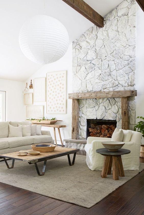 un salon neutre fantaisiste avec beaucoup de texture, une cheminée en pierre blanchie à la chaux avec un manteau en bois rugueux