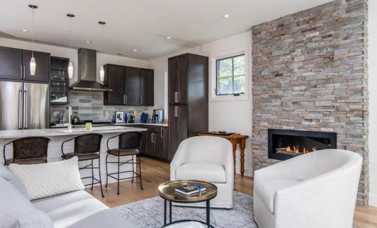 un salon éclectique élégant avec une cheminée intégrée revêtue de fausse pierre, ce qui est une idée de réchauffement cool