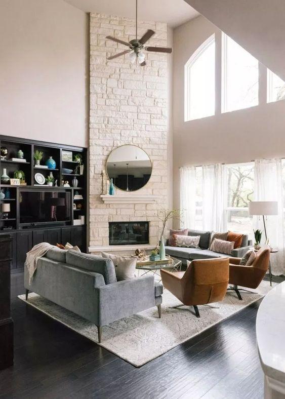 un salon moderne et élégant avec une cheminée d'angle en fausse pierre blanche avec un petit manteau, un miroir rond et des fenêtres à double hauteur