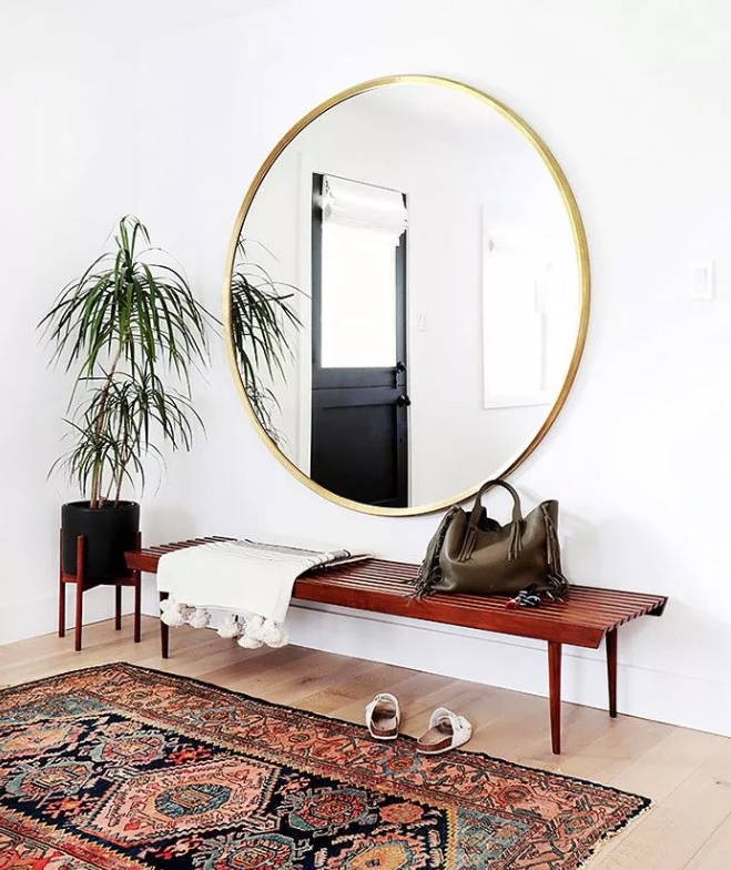 une entrée boho chic avec un banc en bois, un miroir surdimensionné à cadre doré, un tapis boho et une plante en pot