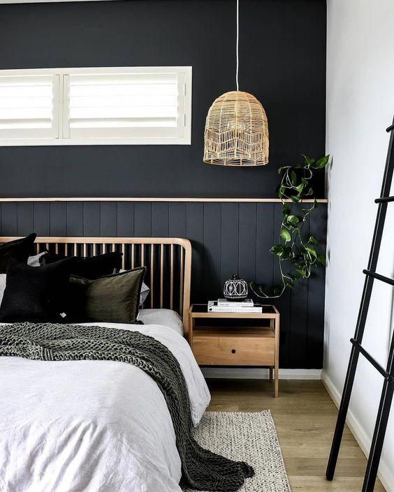 une chambre bohème avec un mur noir fait de panneaux de perles, d'articles en bois, de textiles superposés confortables et de verdure