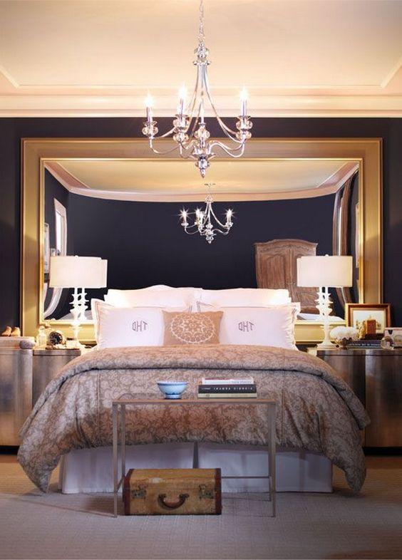 une chambre chic et moderne avec un miroir surdimensionné dans un cadre doré, un lustre chic et quelques lampes pour une ambiance raffinée