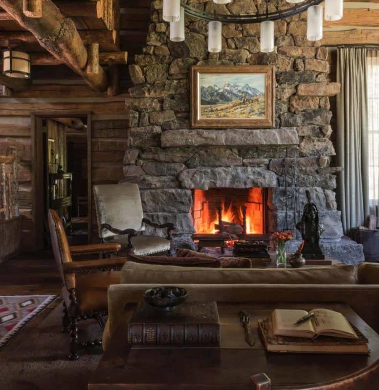 un salon de style cabane fait avec beaucoup de bois brut, un grand foyer en pierre et des meubles vintage en bois et cuir