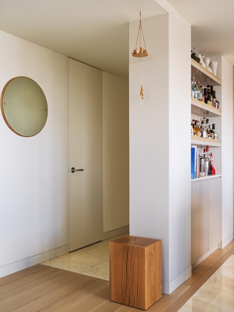 Une unité de bar à foyer ouvert sert également de séparateur d'espace pour séparer l'entrée et la cuisine