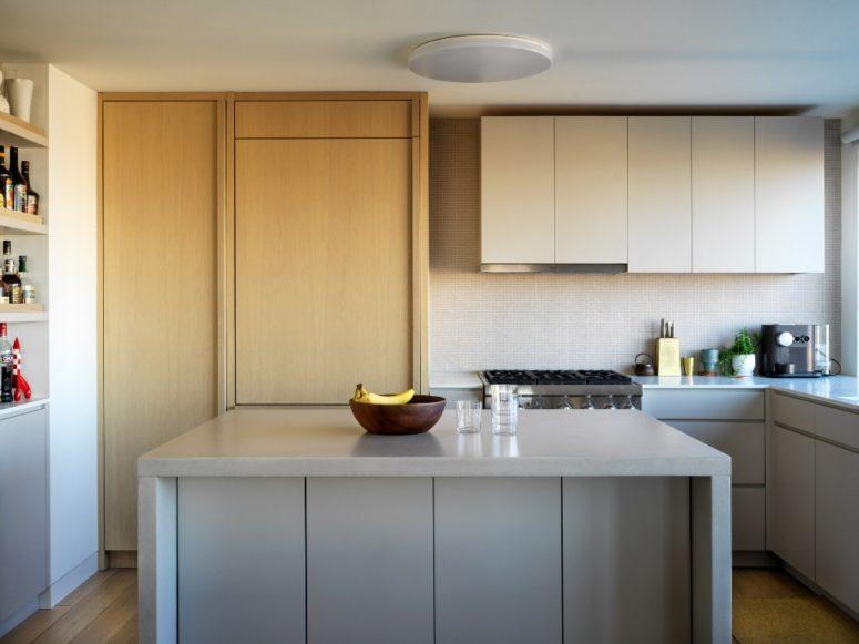 La cuisine est faite dans des tons neutres, avec des surfaces élégantes, des étagères confortables et des unités de rangement principalement cachées