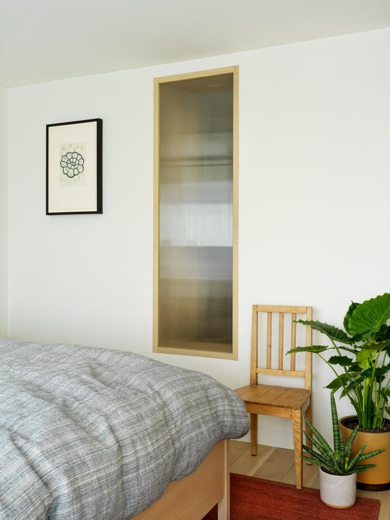 La chambre est aménagée avec des plantes en pot, des meubles simples et confortables et une fenêtre
