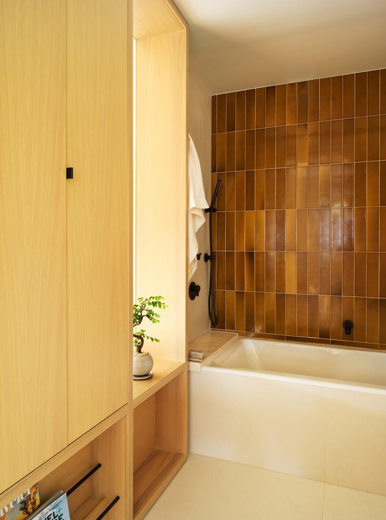 La salle de bain dispose de beaucoup d'espace de rangement caché dans les armoires et les carreaux d'une teinte terreuse très décalée