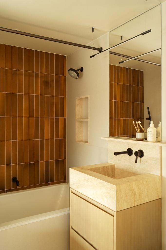 L'évier carré est placé sur une vanité carrée en bois, il y a des luminaires en métal sombre