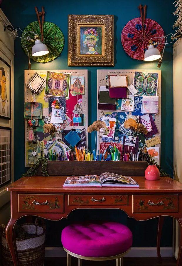 un bureau à domicile boho maximaliste avec un mur d'accent bleu marine, un bureau vintage, un tabouret rose vif, un mur de galerie et des tableaux mémo plus des lumières
