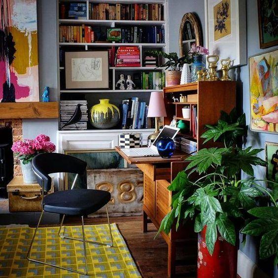 un bureau à domicile maximaliste audacieux avec un mur bleu, une cheminée, un bureau vintage, des œuvres d'art colorées et des plantes en pot