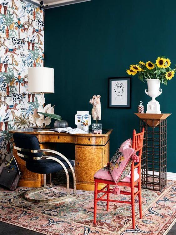 un bureau à domicile maximaliste lumineux avec une sarcelle et un mur de papier peint, un bureau vintage, une chaise marine et une rouge, des textiles colorés et une lampe créative