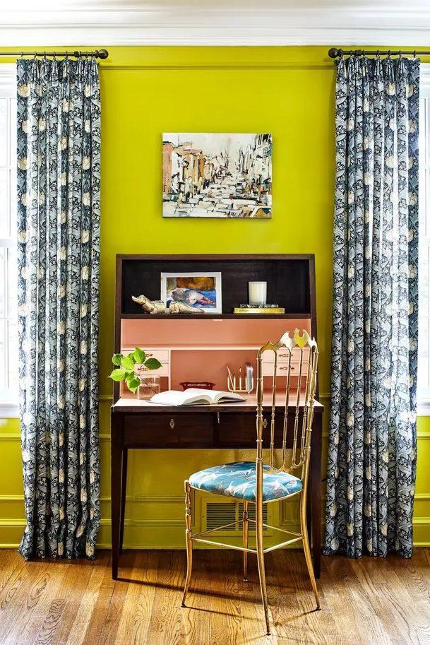 un bureau à domicile lumineux avec des murs jaune fluo, un bureau vintage teinté sombre, une chaise dorée avec un siège tropical et des rideaux imprimés