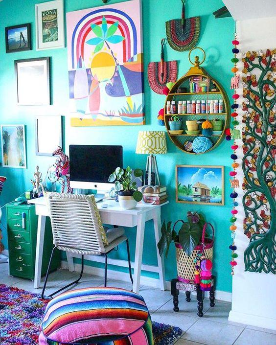un bureau à domicile boho maximaliste avec un mur d'accent turquoise, un bureau blanc, une armoire verte et de nombreuses œuvres d'art et textiles dans des tons audacieux