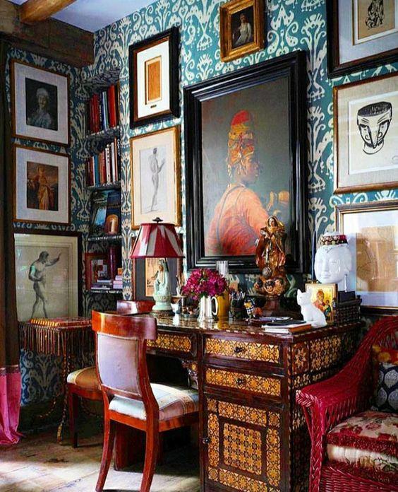 un bureau à domicile maximaliste audacieux avec du papier peint imprimé bleu sarcelle, une galerie sur plusieurs murs, un bureau incrusté, des chaises imprimées audacieuses et une lampe colorée