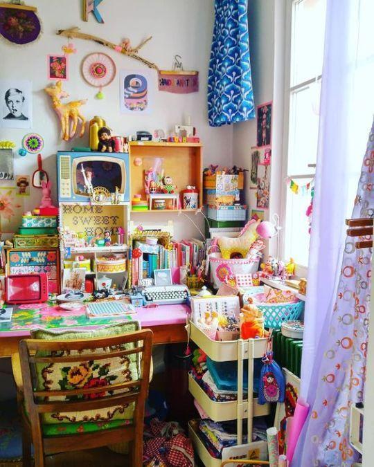 un bureau à domicile maximaliste follement boho avec un bureau rose vif, une chaise verte, des textiles colorés, des accessoires et une décoration est incroyable
