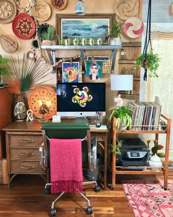 un bureau à domicile coloré avec des murs beiges, un bureau en rotin et un chariot, des paniers décoratifs colorés et un tapis bohème plus une housse de chaise rose