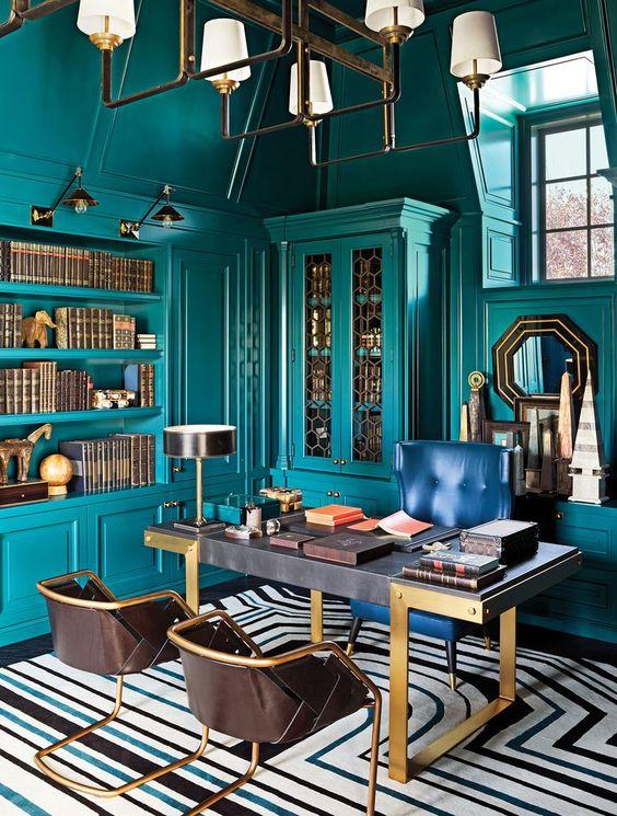 un bureau à domicile maximaliste lumineux avec des murs bleu sarcelle et des meubles et étagères intégrés assortis, un bureau raffiné, des chaises marine et cuir, un lustre chic