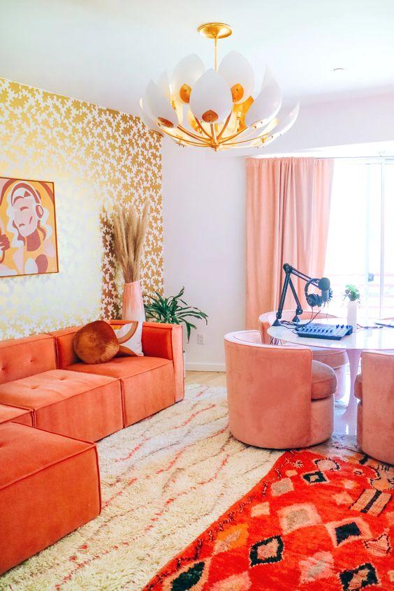 un bureau à domicile maximaliste lumineux avec un mur au pochoir doré, un bureau pour plusieurs personnes, des chaises roses, un sectionnel en corail et des tapis audacieux