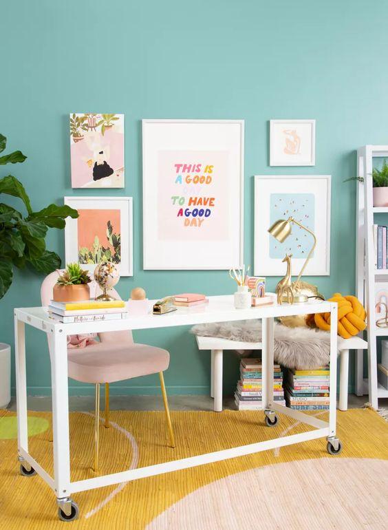 un espace de travail coloré avec des murs turquoise, une chaise blush, un bureau blanc, un tapis coloré et un mur de galerie lumineux