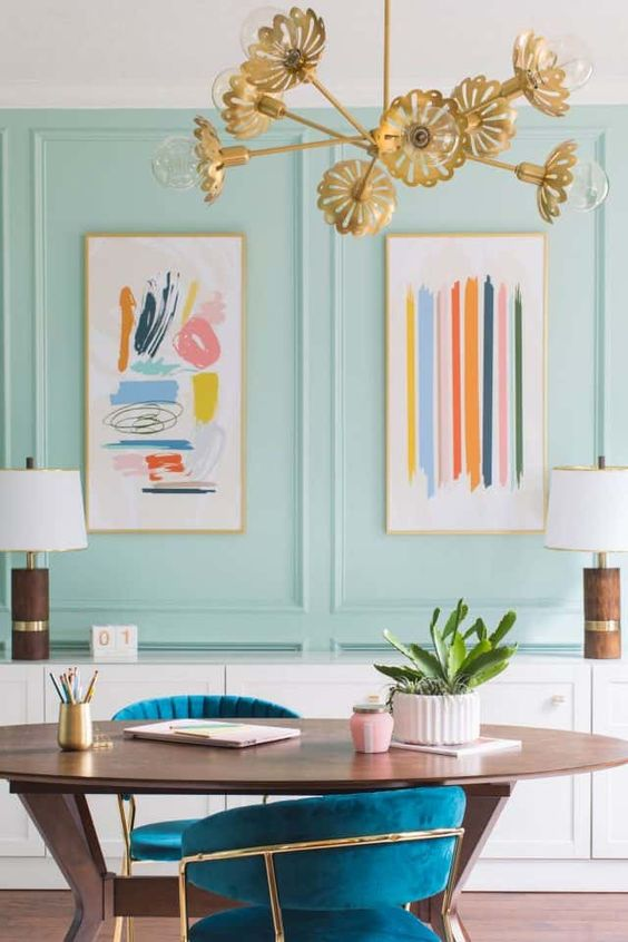 un bureau à domicile maximaliste lumineux avec des panneaux aqua, un bureau ovale et des chaises sarcelle, un lustre floral doré et de jolies œuvres d'art