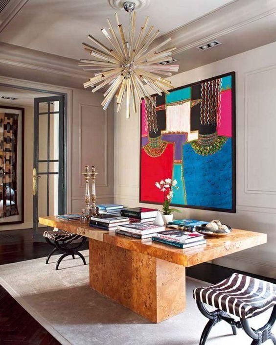 un bureau à domicile maximaliste avec un grand bureau partagé, des livres colorés, une œuvre d'art audacieuse, des chaises imprimées et une lampe sunburst