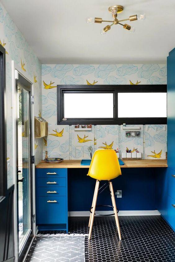 un bureau à domicile maximaliste avec un sol en carrelage, un bureau bleu vif, un joli papier peint imprimé, un tabouret jaune et un lustre doré
