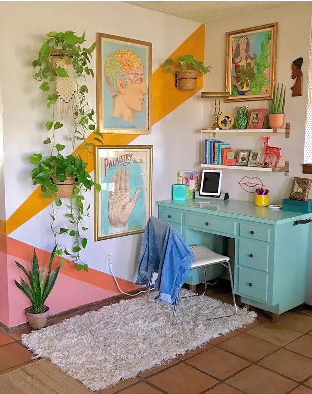 un bureau à domicile maximaliste avec un mur d'accent de bloc de couleur, un bureau turquoise, des étagères flottantes, des œuvres d'art colorées et de nombreuses plantes en pot