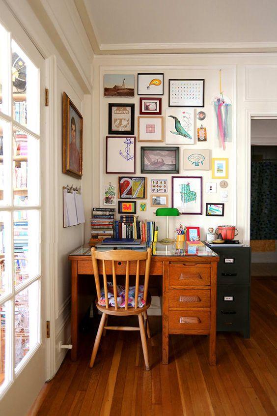 un bureau à domicile maximaliste avec un bureau et une chaise vintage, un mur de galerie coloré et des livres audacieux et une lampe de table