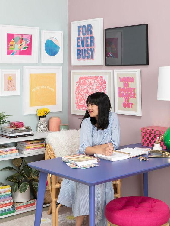 un bureau à domicile maximaliste pastel avec un mur de galerie coloré, un bureau lilas, un tabouret rose vif, des livres pastel et une lampe