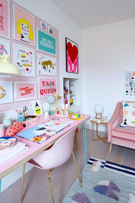 un bureau à domicile pastel pastel avec un mur d'accent blush et un mur de galerie coloré, un bureau rose et une chaise rose, un canapé rose et des textiles colorés