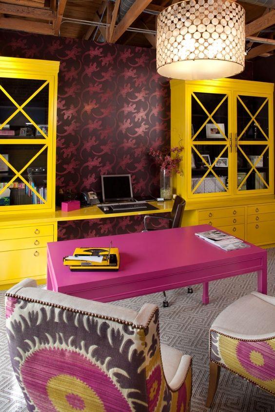 un bureau à domicile maximaliste avec du papier peint audacieux, un bureau rose vif et des unités de rangement jaunes audacieuses, des chaises colorées et une suspension