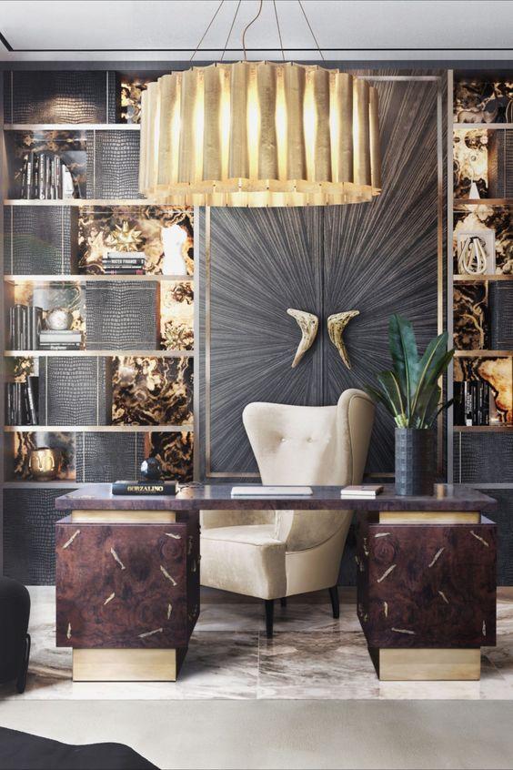 un bureau à domicile sophistiqué avec un mur doré et noir, des étagères, un bureau sombre et une grande chaise à oreilles, une suspension dorée