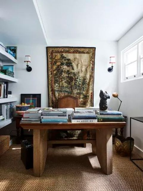 un bureau à domicile maximaliste raffiné avec des murs blancs, des étagères flottantes, un bureau en bois brut, un tapis en jute, des paniers et des tables et une tapisserie