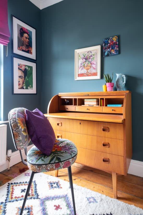 un coin de travail maximaliste avec des murs gris, un bureau vintage, une chaise colorée et des textiles audacieux ainsi qu'un mur de galerie lumineux
