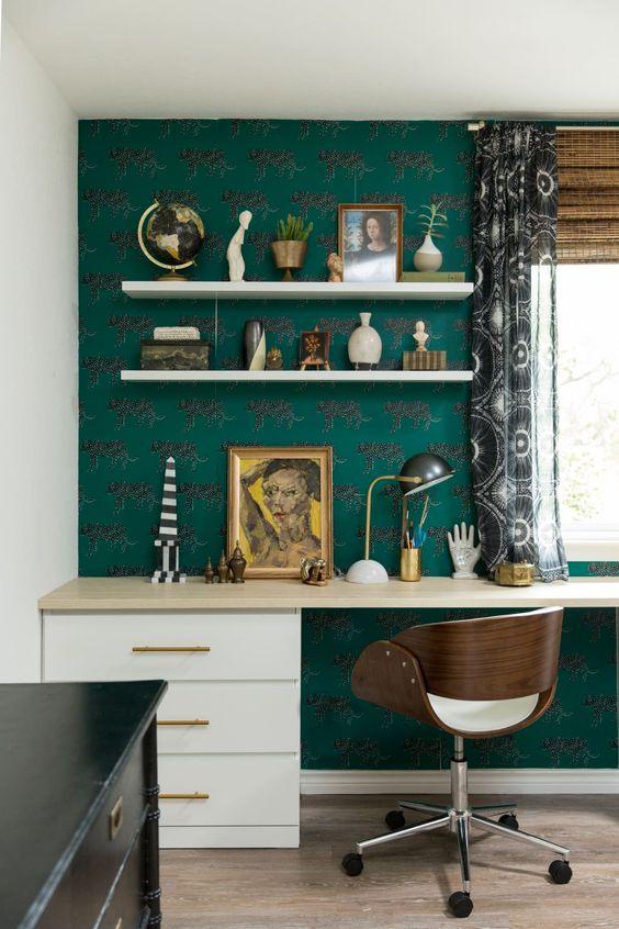 un élégant bureau à domicile maximaliste avec un mur de papier peint vert, un grand bureau, une chaise confortable, une commode noire, de nombreux accessoires et des rideaux imprimés